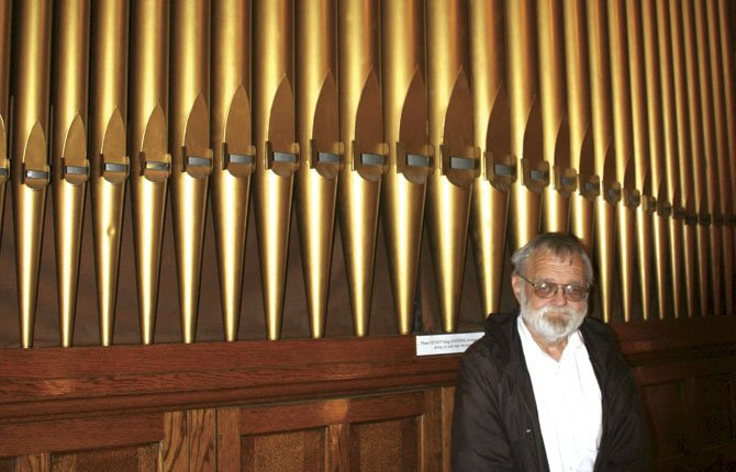 ROBERT CARSNER, organizer of the biennial Organ Crawl in The Dalles, poses March 19 with the visible pipes of the 1907 Kilgen Organ at St. Peter's Landmark.