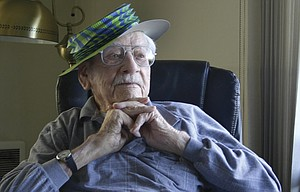 EDGAR ASHBRENNER, wearing a party hat, pays close attention to musicians at his early 105th birthday party March 21. He turns 105 Sunday, March 24.
