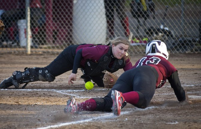 THE DALLES WAHTONKA catcher Katherine Kramer, left, loses control of the ball as she dives to intercept Redmond High School base runner Amanda Cain at home plate late in the sixth inning of Friday's varsity softball game in The Dalles. Cain's run proved to be the eventual game-winner as the Lady Panthers rallied from a three-run deficit to defeat TDW by a 5-4 margin.