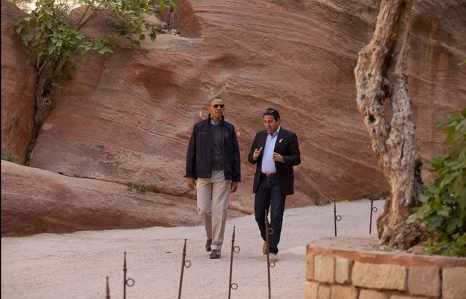U.S. President Barack Obama walks with Dr. Suleiman A. D. Al Farajat, right, a tourism professor with the University of Jordan, through the Siq during a visit to the ancient city of Petra, in south Jordan March 23.