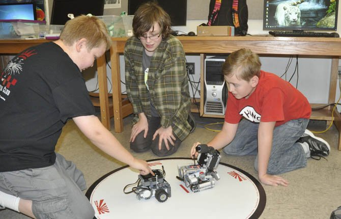 Spencer Glenn, Calvin Kane and Nathanial Brown (left to right) prepare their Sugo Bots for battle. The robots are a new addition to this year's 4-H tech group that students can attend after school.