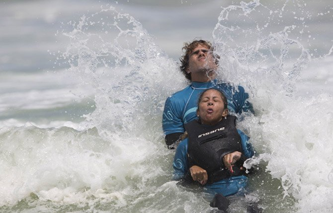 Monique Oliveira is aided by an AdaptSurf volunteer as a wave breaks at Barra da Tijuca beach in Rio de Janeiro, Brazil March 16. AdaptSurf is a Rio-based non-governmental organization that aims to make beaches accessible to the disabled and encourage them to practice water sports. The organization is the first of its kind in Brazil.