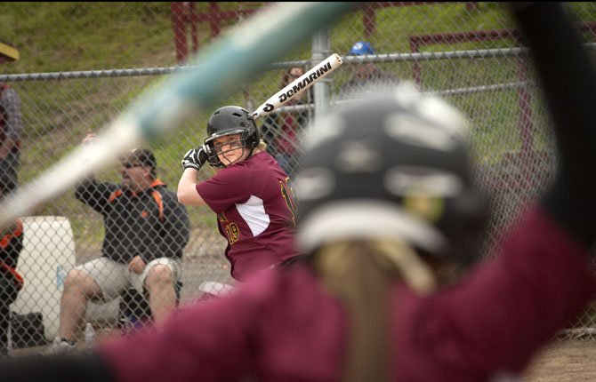 TDW senior Melanie Taphouse (rear) watches her coach Steve Garrett (not pictured) as she takes a couple of practice swings between pitches in Tuesday's tournament softball game against Molalla. Against Molalla, Taphouse went 3 for 4 with two doubles, two runs scored and two RBIs in the Tribe's 9-4 win. In two games Tuesday, TD rapped out 26 hits and outscored Molalla and Gresham by a combined 22-7 margin.