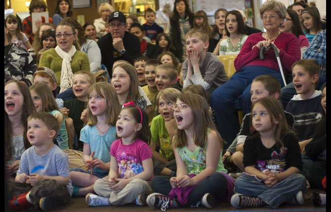 A crowd of kids interacts with Alex Zerbe as he performs at The Dalles Wasco County Library Wednesday, March 27, for a Spring Break show. Zerbe is a two time Guinness World record holder, voted funniest prop comic.