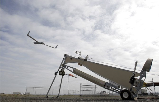 AN INSITU ScanEagle launches an unmanned aircraft March 26 at the airport in Arlington. Federal and state officials believe it's a good bet that in the not-so-distant future aerial drones will be part of Americans' everyday lives, performing countless useful functions.
