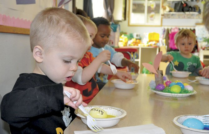 PRESCHOOLER PATRICK, foreground, concentrates on the egg that is turning yellow in a bowl of dye as his classmates, from left, Ben, Brandon and Sam do the same March 28 at Great and Small child care in The Dalles.