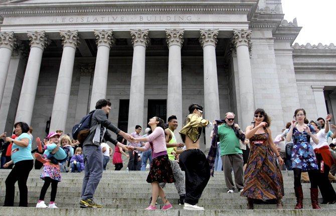 People dance on the steps of the Capitol in Olympia, Wash., Monday, April 1, 2013 to protest a decades-old state tax on dance venues. Washington state has had the tax, which targets venues that provide an opportunity to dance, since the 1960s. A measure to repeal it has cleared a committee and is awaiting a floor vote in the Senate.