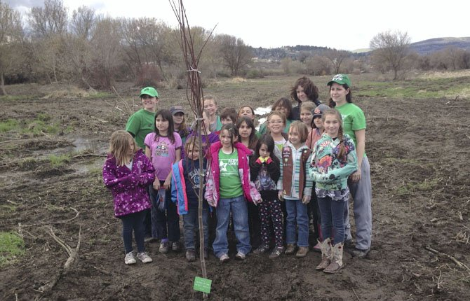 Girl Scouts from Troop 50121 gather around a tree they planted at Riverfront Park during a recent service project.