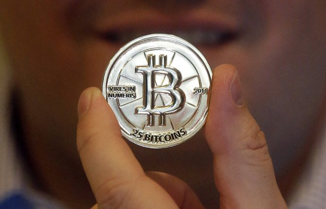 Mike Caldwell, a 35-year-old software engineer, holds a 25 Bitcoin token at his shop in Sandy, Utah. Caldwell mints physical versions of bitcoins, cranking out homemade tokens with codes protected by tamper-proof holographic seals, a retro-futuristic kind of prepaid cash.