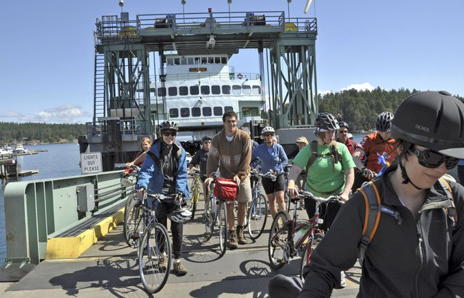 Cyclists debark at Friday Harbor on San Jan Island. They get on and off the ferries ahead of the motor vehicles. Cyclists going to the San Juan Islands from Anacortes pay the passenger fare plus a $2 surcharge during the non-peak times (October 1-April 30) and a $4 surcharge during the peak season (May 1-September 30). After paying the initial round-trip fare, inter-island travel is free.
