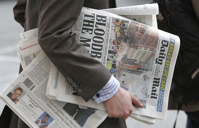A man carries newspapers featuring the Boston marathon blasts on the front page, while waiting to cross a road in central London, April 16. British police are reviewing security plans for Sunday's London Marathon, the next major international marathon.
