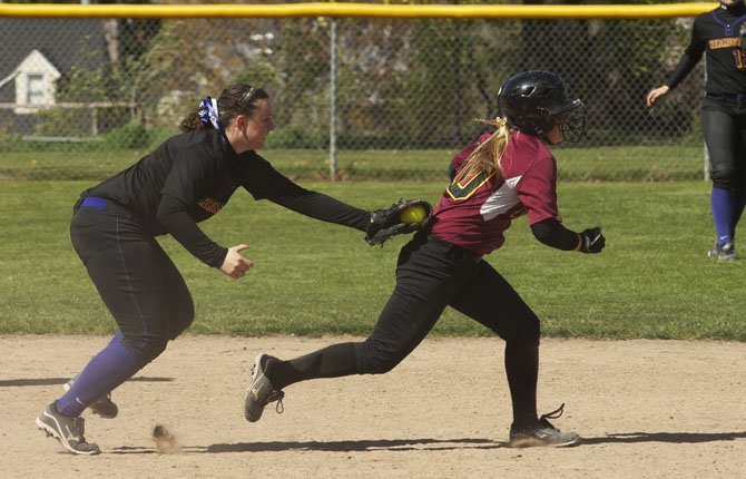Morgan Triperinas, right, is run down by Hermiston's pitcher during the second game of a double header Saturday, April 13.