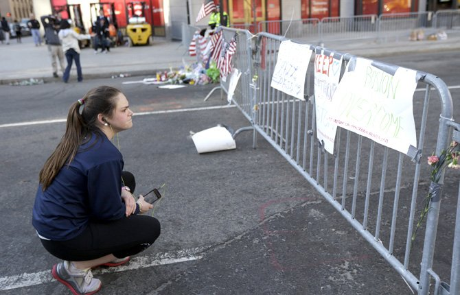 Cailly Carroll reads signs posted on a barricade, Wednesday, April 17, 2013, in Boston. The city continues to cope following Monday's explosions near the finish line of the Boston Marathon.