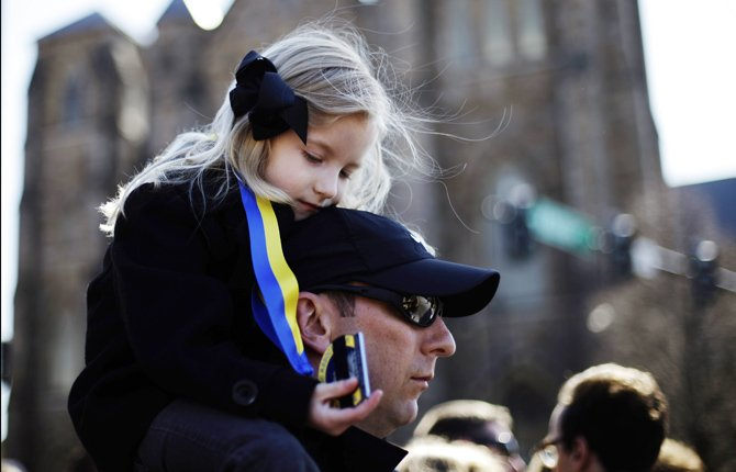 Marathon runner Nathan Finney of Boston and his daughter Mckenna, 5, gather with others ahead of an interfaith service with President Barack Obama at Cathedral of the Holy Cross.