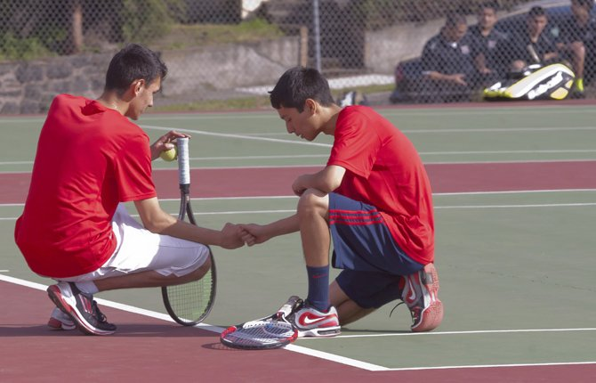 Chara Vasquez, left, and Jose Santillan tap knuckles in solidarity as they take a short break between sets during Tuesday's competition in The Dalles April 16.