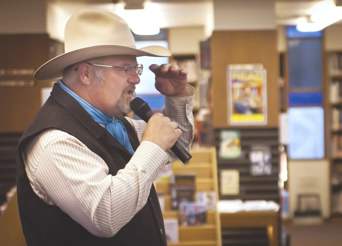 "Local cowboy poet Duane Lee Nelson recites a poem at The Dalles Wasco County Public Library Wednesday evening, April 17, as a prelude to ""Cowboy Poetry Week"" April 21-27. He is adjusting his cowboy hat, a surprisingly useful measuring device if the aforementioned cowboy poet is to be believed."