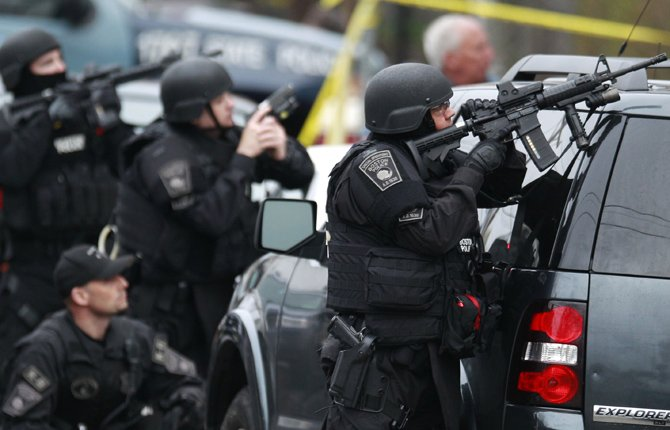WATERTOWN, Mass. (AP) — The two suspects in the Boston Marathon bombing killed an MIT police officer and hurled explosives at police in a car chase and gun battle overnight that left one of them dead and his brother on the loose, authorities said Friday as thousands of officers swarmed the streets in a manhunt that all but paralyzed the Boston area
