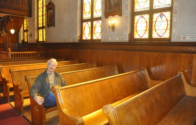 DOUG LEASH sits in the former nave of St. Peter's Landmark, which is distinguished by multiple stained glass windows and other ornate ornamentation. The Landmarks' preservation committee has the stained glass windows refurbished one by one as funds become available.