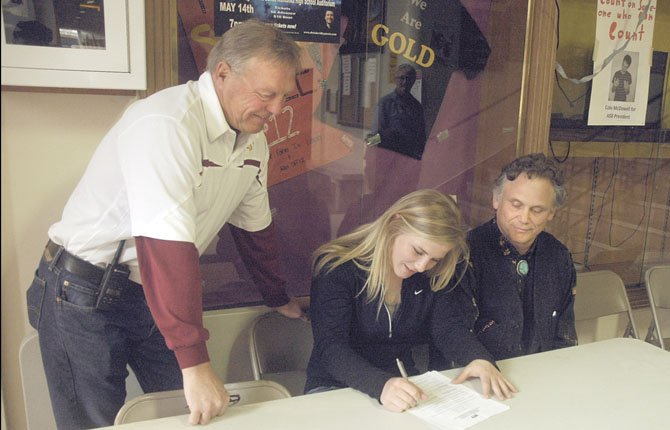 The Dalles Wahtonka'S Katherine Kramer (middle) signs her national letter of intent to play softball at the University of Pittsburgh this past Thursday in the main foyer of the high school. Kramer is flanked by head coach Steve Garrett (left) and her father, Kevin Kramer. The perennial all-league and all-state softball player received a half scholarship and will major in dental hygiene.