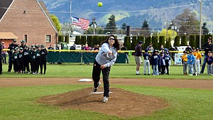 Raquel VanNatta, who once played on local Little League teams, tosses the opening pitch of the season Saturday.