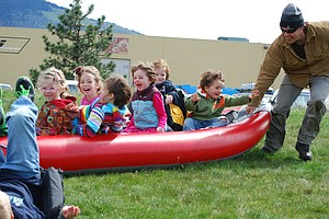 Wild smiles and hard work mixed at Hood River Waterfront Park on Saturday when Earth Day revelers and volunteer gardeners joined together for the day-long events. Cascadia Adventure Educational School provided the fun for tots with teacher Matt Farmer shown here spinning would-be future kayakers into a frenzy.