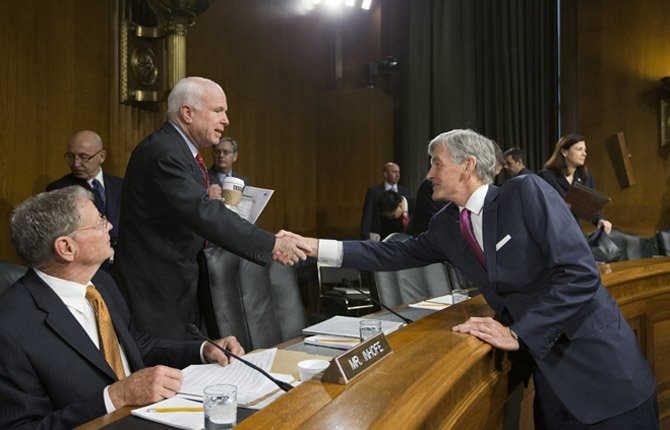 SENATE ARMED Services Committee member Sen. John McCain, R-Ariz, center, greets Army Secretary John McHugh, right, on Capitol Hill in Washington, April 23, prior to McHugh testifying before the committees hearing on the Defense Department budget requests for fiscal year 2014. At left is Sen. James Inhofe, R-Okla., the ranking member of the committee.
