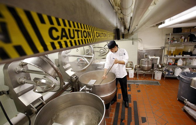 Sous Chef Shawn Savage stirs a kettle in the University of Oregon central kitchen in Carson Hall April 18. Above his head is low-hanging duct work with caution signs to help prevent banged heads in the kitchen that opened after World War II.   The university plans to replace it with a new $8.5 million kitchen. A new campus central kitchen is expected to displace University of Oregon student renters in a dozen tiny cottages put up after World War II.
