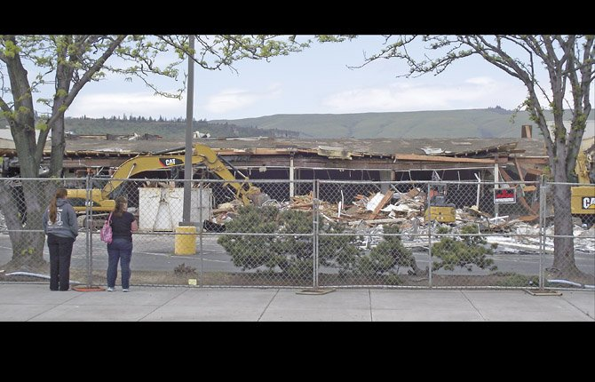 SPECTATORS WATCH as heavy equipment bites into the former Albertsons supermarket building at West Sixth and Cherry Heights. Goodwill has indicated an intent to build a store and other commercial space on the site.