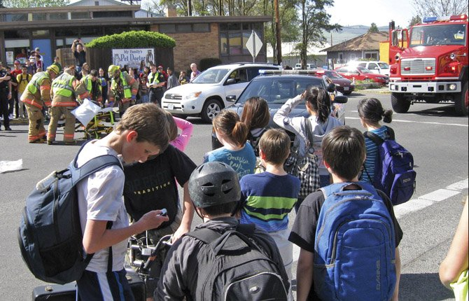 A CROWD of students heading home from school gathered at 12th and Kelly streets Thursday afternoon where an injury crash occurred. The report was called in at 3:16 p.m. A 14-year-old boy was transported by ambulance to Mid-Columbia Medical Center after he was struck by a passing car.