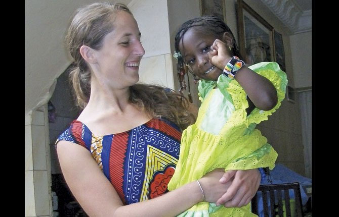 Amy Krol stands with a young child during a Senegal wedding ceremony.