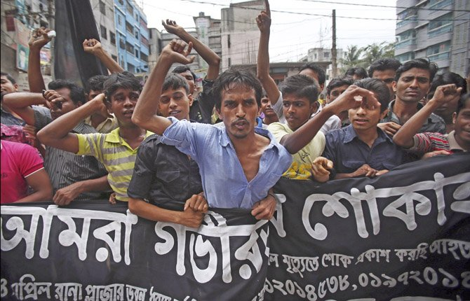 Workers at a garment factory just streets away from the recently collapsed garment factory building, protest as they refuse to work when they found cracks in their current office building, April 30, in Savar, Bangladesh.