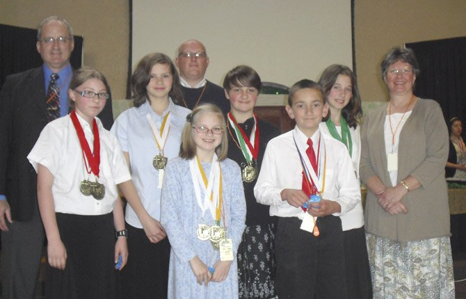 Students from Sonrise Academy won a number of medals while attending the Pacific Northwest Accelerated Christian Education Convention. Left to right are: (front row) Sarah Winters, Mike DePaepe, (center row) McKenzie Johnson, Kim Winters, Halie Beall, Bailey Nearing, Debbie Winters (back row), Principal Scott Winters and Pastor Andy Johnson.