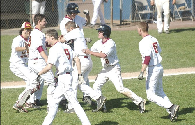 THE DALLES WAHTONKA senior Justin Sugg (middle) is mobbed by his jubilant teammates after driving in Hunter Malcolm (9) with an RBI single in the bottom of the seventh inning to vault the No. 4-ranked Tribe to a 12-11 victory and the two-game Columbia River Conference baseball sweep Saturday in The Dalles.