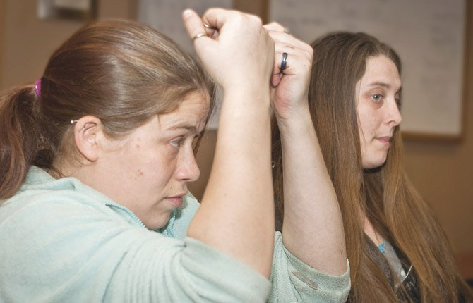 KATHRYN Riter, left, demonstrates how she ended up with arm and hand wounds while attempting to ward off hammer blows that were allegedly struck by Brian DePriest, an ex-boyfriend, prior to the Jan. 23 kidnapping of her son. Riter's sister, Amber Tyler, has become her advocate at legal proceedings and when dealing with family service agencies and media representatives.