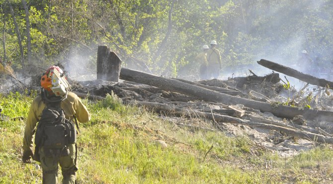 A firefighter lugs a chainsaw across his shoulder as he joins fellow firefighters in knocking down fuels beyond a backfire where a burn pile spread out of control.