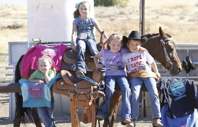 LOCAL RODEO youngsters (pictured from left to right), Ava Malcolm,4, Madi Malcolm, 8, Nellie Wilkinson 5, and Klayton Schanno, 5, bask in the glory of winning awards last season. This group is headed to Prineville Saturday for the 2013 opening event of Central Oregon Peewee Rodeo Association action.