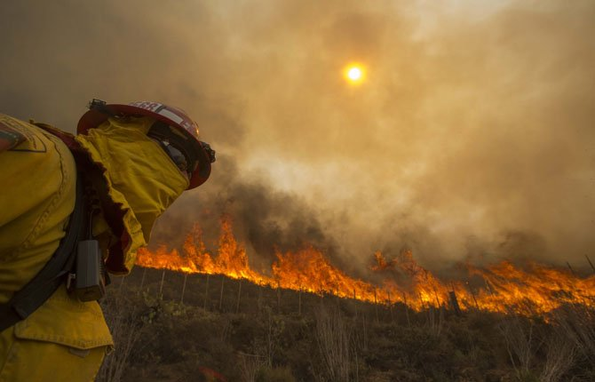 Weather may aid firefight A firefighter keeps watch as the wildfire burns along a hillside May 3 in Point Mugu , Calif.Firefighters got a break as gusty winds turned into breezes, but temperatures remained high and humidity levels are expected to soar as cool air moved in from the ocean and the Santa Ana winds retreated.