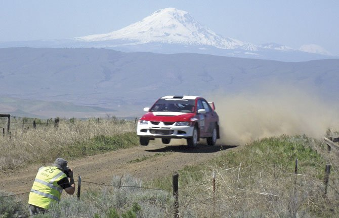 A PHOTOGRAPHER captures the action as a driver grabs air beneath a looming view of Mt. Adams during Sunday action on the rural roads near Dufur, part of the Oregon Trail Rally held in Portland, Hood River County and Wasco County this weekend.