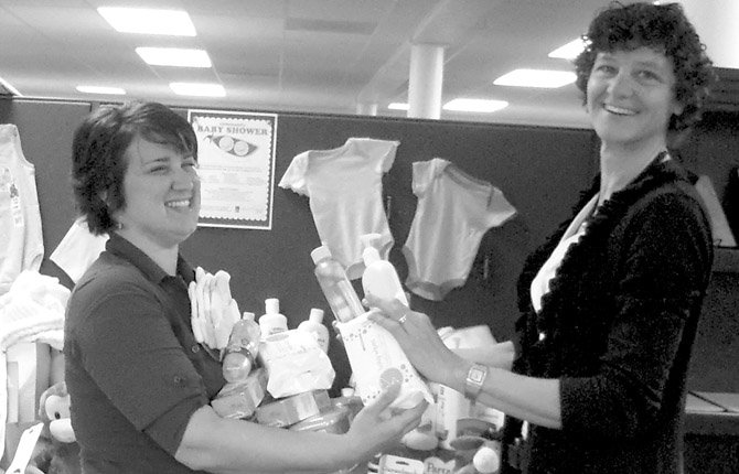 BABY GIFTS GALORE grace the tables at the Soroptimist Community Baby Shower final round-up party in 2011. Families First and New Parent Services staff Elisa Cartwright and Karen Enns are overjoyed with the prospect of being able to help so many young families in need. This year's shower runs until May 17 in Hood River and The Dalles.