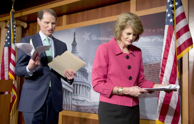 Sen. Ron Wyden, D-Ore., left, follows Sen. Lisa Murkowski, R-Alaska as they leave the podium after a news conference on Capitol Hill in Washington, April 23, to discuss campaign finance reform.