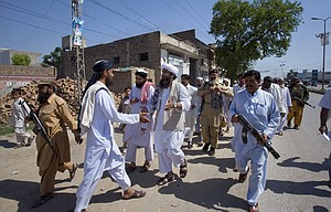 """MAULANASHUJAUL Mulk, center, pro-Taliban Jamiat-e-Ulema Islam (JUI-F), is surrounded by guards as he greets a supporter during his election campaign at a road in Mardan, Pakistan. Mulk is among several Pakistani Islamists and sectarian groups contesting for the country's upcoming parliamentary elections, which are divided and scattered though, they are still in a position to secure enough strength to play Pakistani establishment bid to """"hound"""" the next frail government in influencing its decisions about the U.S. forces withdrawal from Afghanistan in 2014."""