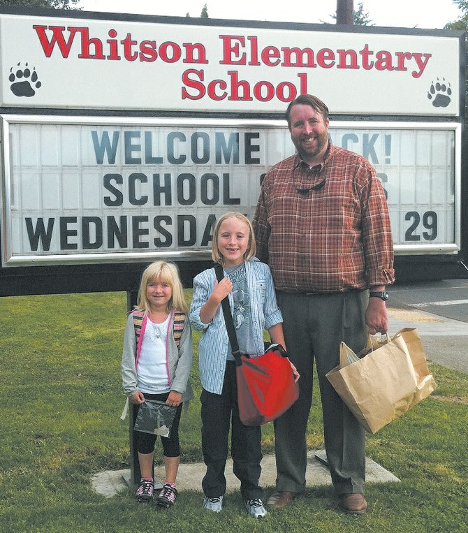 Todd McCauley stands outside Whitson Elementary on the first day of school last year with his daughter, Lilly (far left), and his son, Sawyer, who attend kindergarten and third grade at the school, respectively. Currently the vice principal of Hood River Valley High School, McCauley was recently hired as the new principal of Whitson.