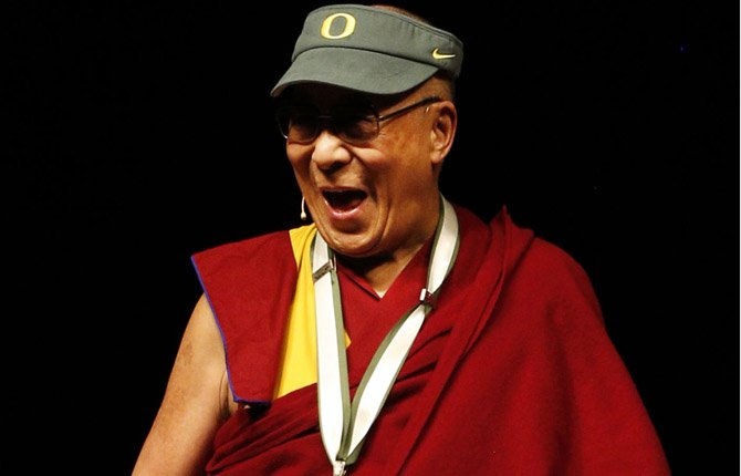 The Dalai Lama jokes with the crowd after receiving an Oregon Duck visor at Matthew Knight Arena during his visit May 10 to Eugene.