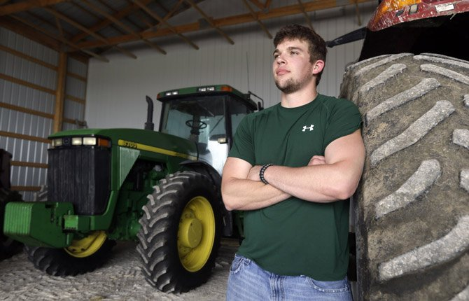 Jake Anderson poses for a photo in an equipment shed on his family's farm in Williamsburg, Mo. Anderson didn't have to delve too deep into the University of Missouri's agricultural economics program before realizing he was destined to return to the 1,500-acre family farm. After all, that's been the Anderson family trade since 1891.