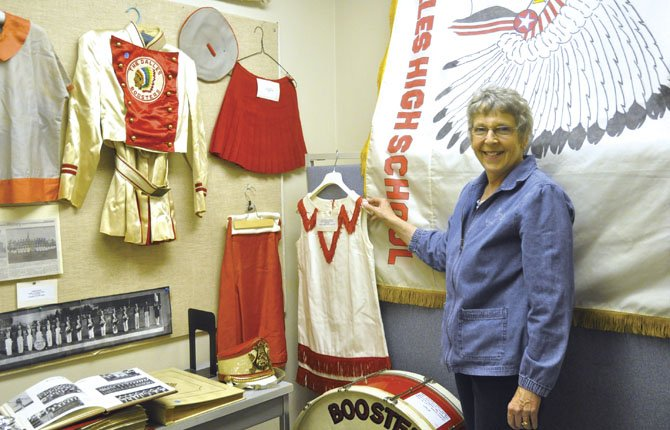 Joy Krein, a volunteer at the School District Archives Museum, shows off a booster girl uniform on display that is identical to one she wore as a booster girl.