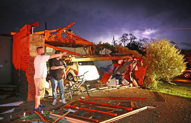 Derrek Grisham, left, points out neighborhood damage to storm chaser Travis Schafer after a tornado damaged his mother's house on Hyde Park Lane at Country Club Rd. in Cleburne, Texas, May 15. Cleburne Mayor Scott Cain early Thursday declared a local disaster as schools canceled classes amid the destruction.