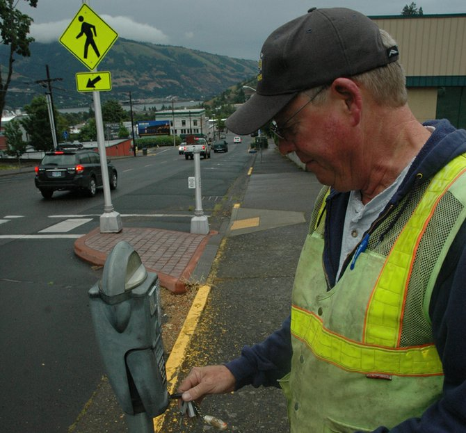 Parking meters on poles will be replaced with kiosks on State Street under the project. City worker Steve Hughes removes coins on Friday morning.