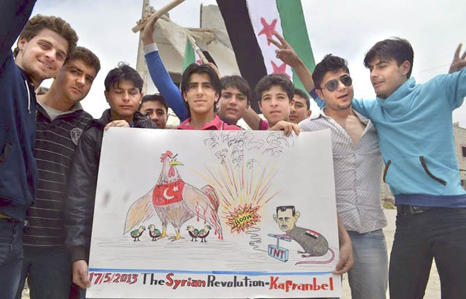 THIS CITIZEN journalism image provided by Edlib News Network, ENN, which has been authenticated based on its contents and other AP reporting, shows anti-Syrian regime protesters holding a placard with a caricature of Syrian President Bashar Assad during a demonstration in Kafr Nabil, in Idlib province May 17. Rights activists have found torture devices and other evidence of abuse in government prisons in the first Syrian city to fall to the rebels, Human Rights Watch said in a report Friday.