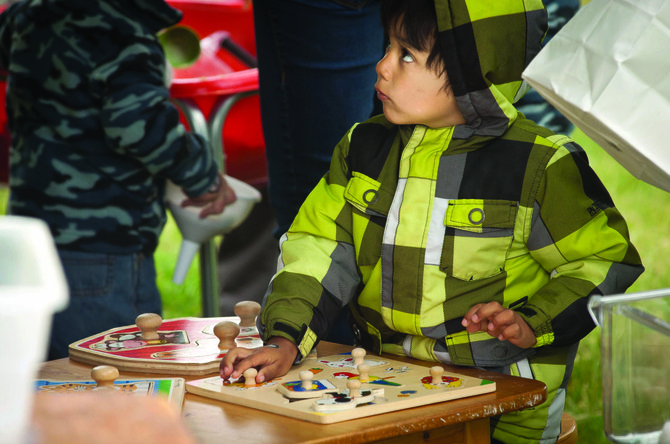 JOSE CASTRO, 4, plays with a puzzle at the Children's Fair in City Park Saturday, May 18. The table was run by Columbia Gorge Education 