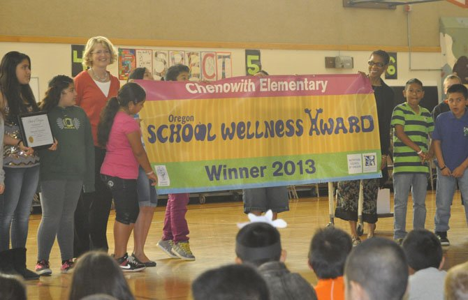 Students at Chenowith Elementary School unfurl a banner proclaiming the school one of three winners of the 2013 Oregon Wellness Award